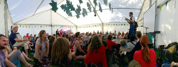The Underground Clown Club perform to a large crowd in a sunny tent at Greenbelt Festival